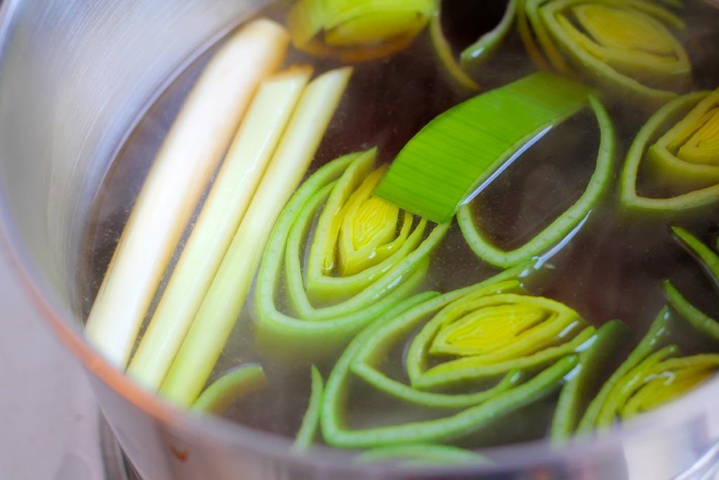 Gebackener-Porree-mit-Shitale,-Sake-und-Muscheln-Sosse-einkochen